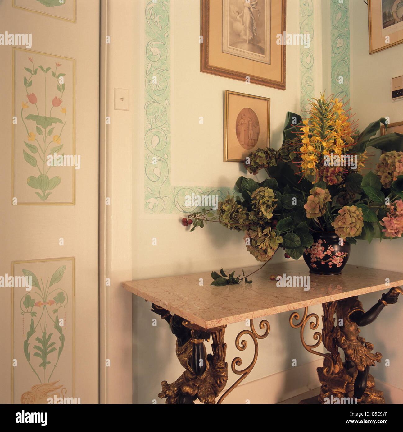 Flower Arrangement On Marble Topped Ornate Gilt Table In Corner Of Hall  With Painted Floral Decorations