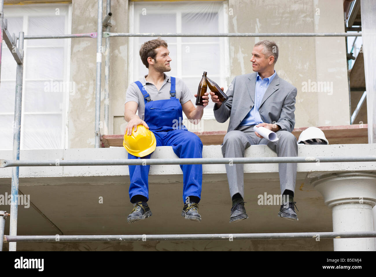 architect and construction worker on site, drinking beer stock