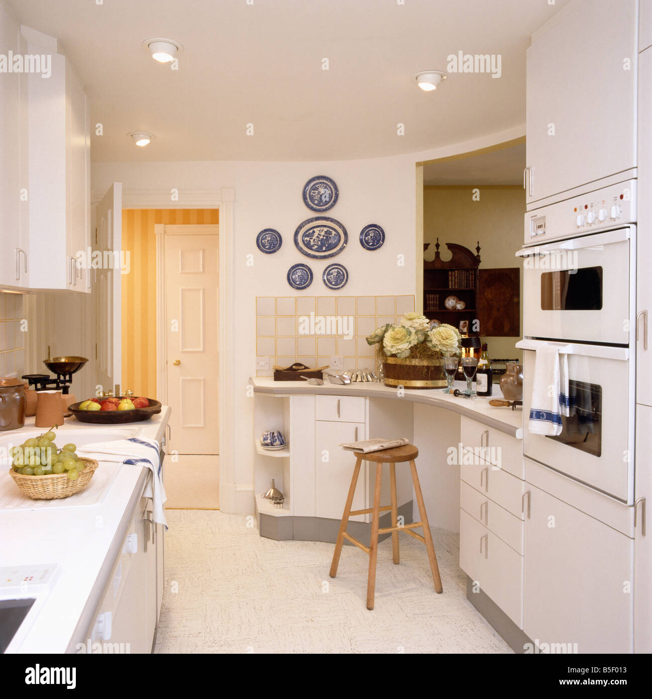 Wooden stool and eye level oven in modern white kitchen for Eye level oven kitchen designs