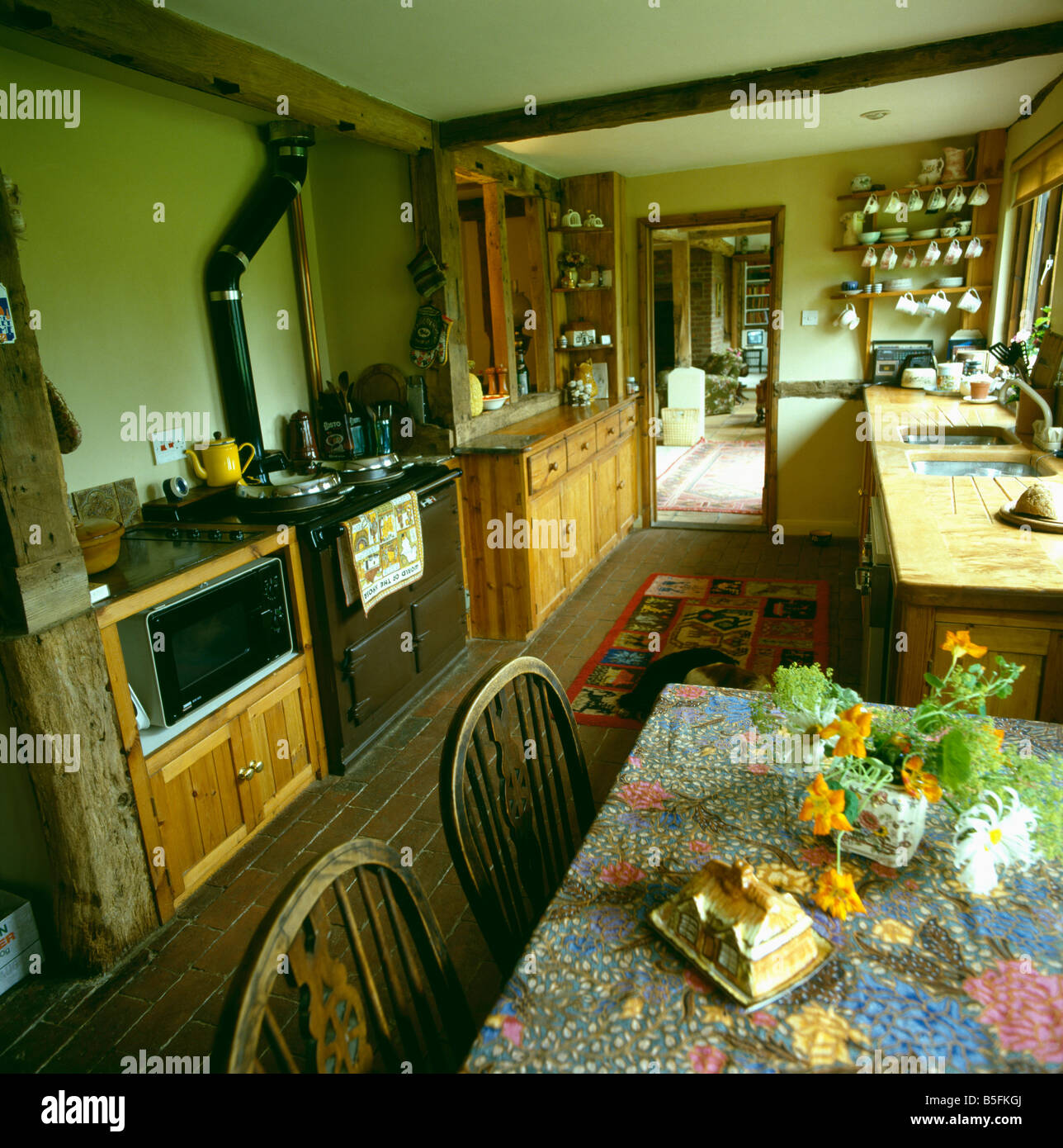 Rayburn Oven In Old Fashioned Country Kitchen With Floral Cloth On Table  And Microwave Fitted Into Pine Unit Part 71