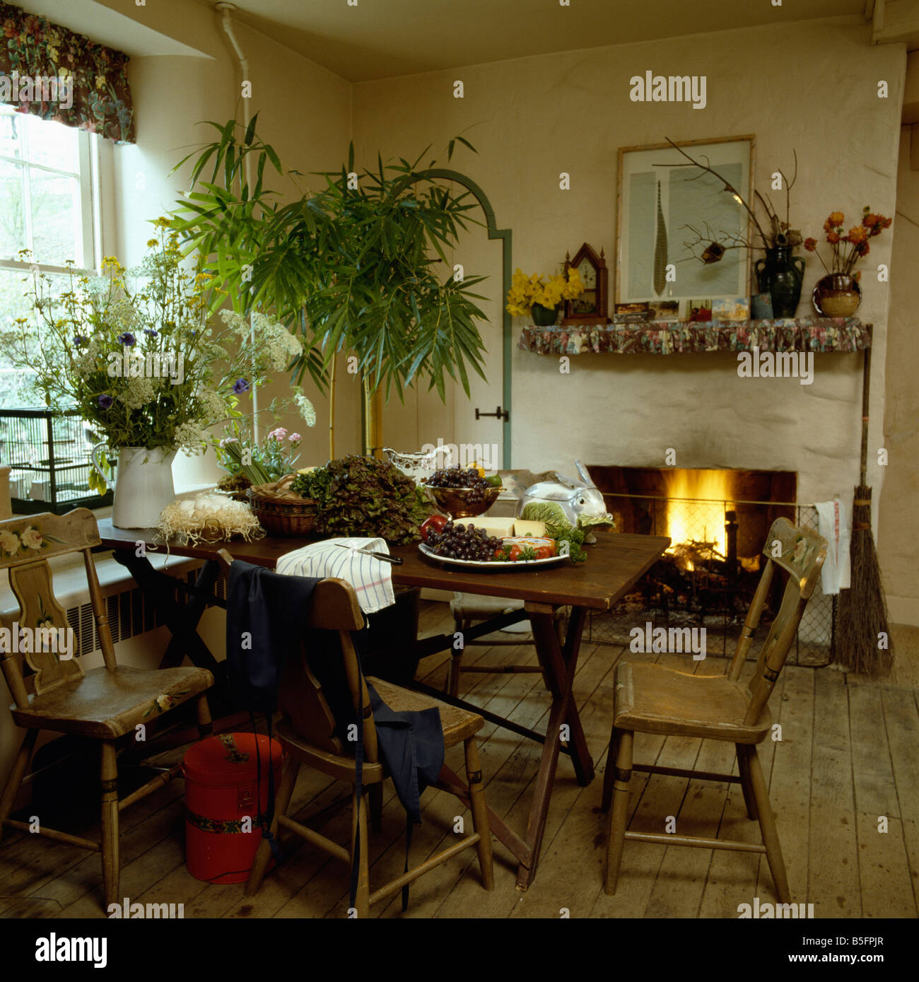 Lighted Fire In Fireplace And Food On Wooden Table With Matching Chairs Simple Country Dining Room Green Houseplant