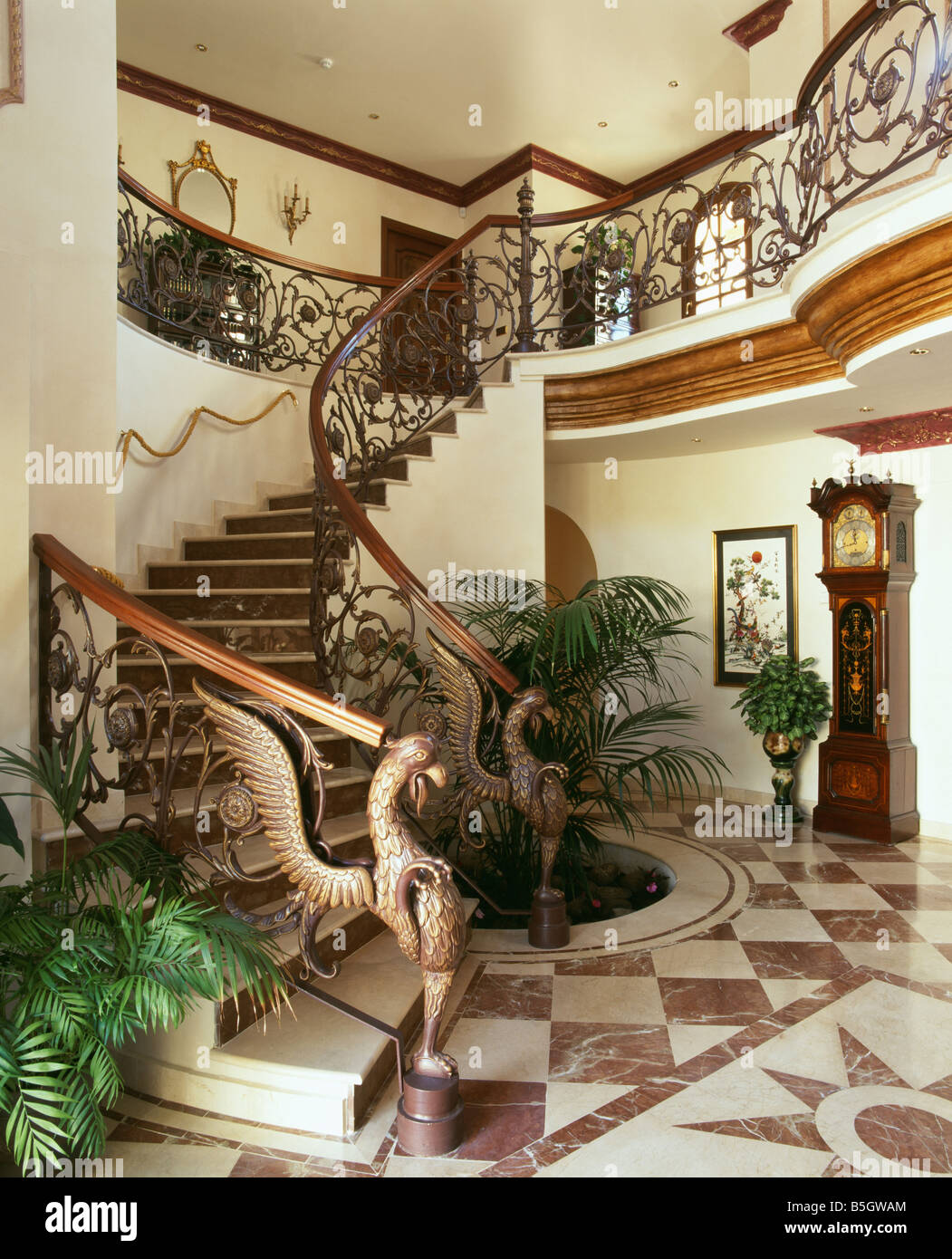 Traditional spanish tiling stock photos traditional spanish ornate wrought iron bannisteers on curved staircase in spanish hall with brown white marble dailygadgetfo Images