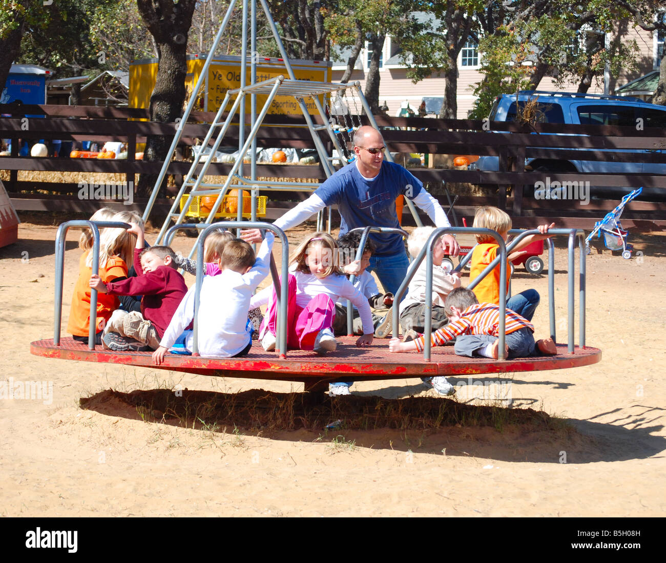 Father Pushing Kids On A Merry Go Round At Playground