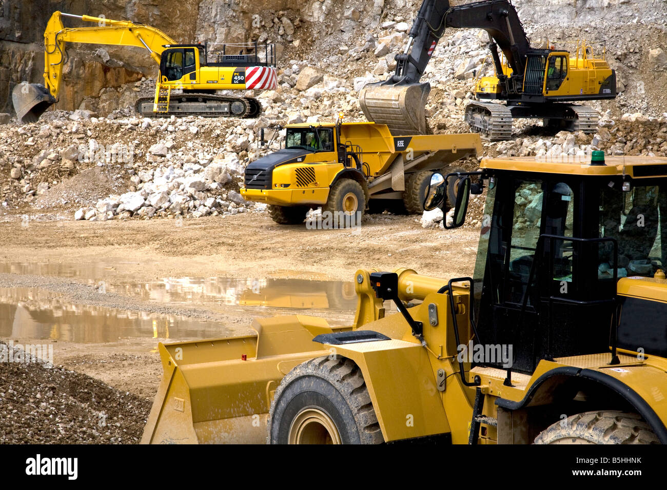 scene in a busy quarry showing diggers excavators dumpers and