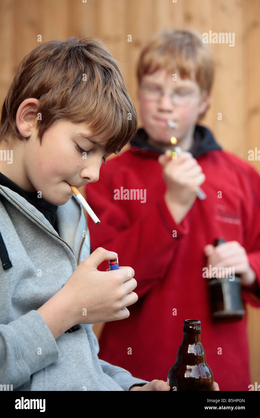 underage smoking Portrait of two underage boys smoking and drinking beer - Stock Image