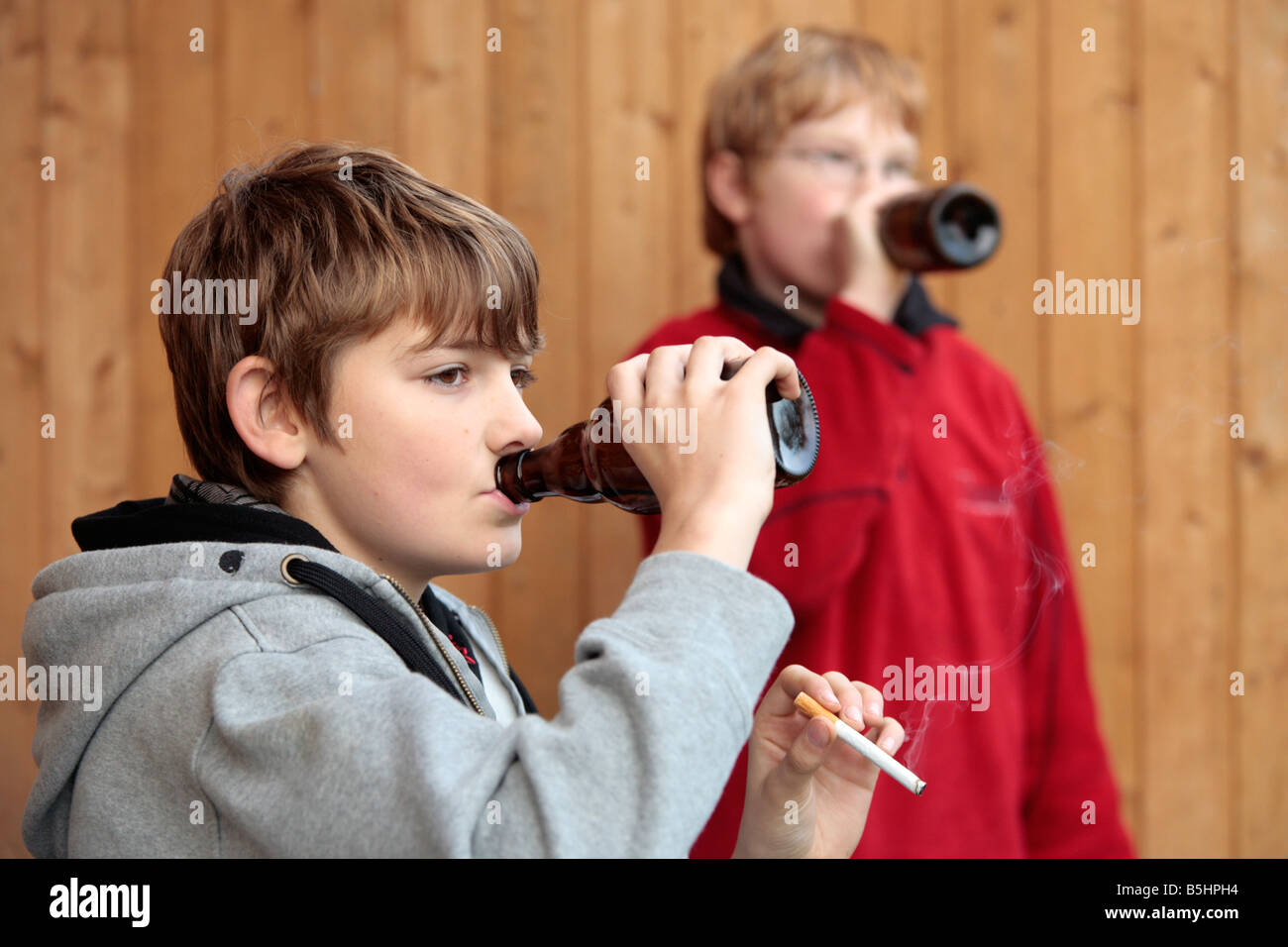 underage smoking ... Portrait of two underage boys smoking and drinking beer - Stock Photo