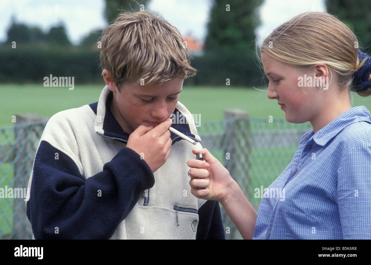 teenage girl lighting cigarette for young boy in park  sc 1 st  Alamy & teenage girl lighting cigarette for young boy in park Stock Photo ... azcodes.com
