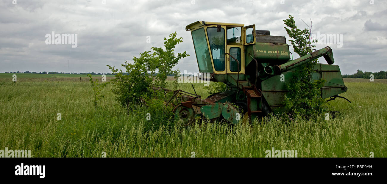 An old John Deere Combine sits in a field of weeds Stock ...