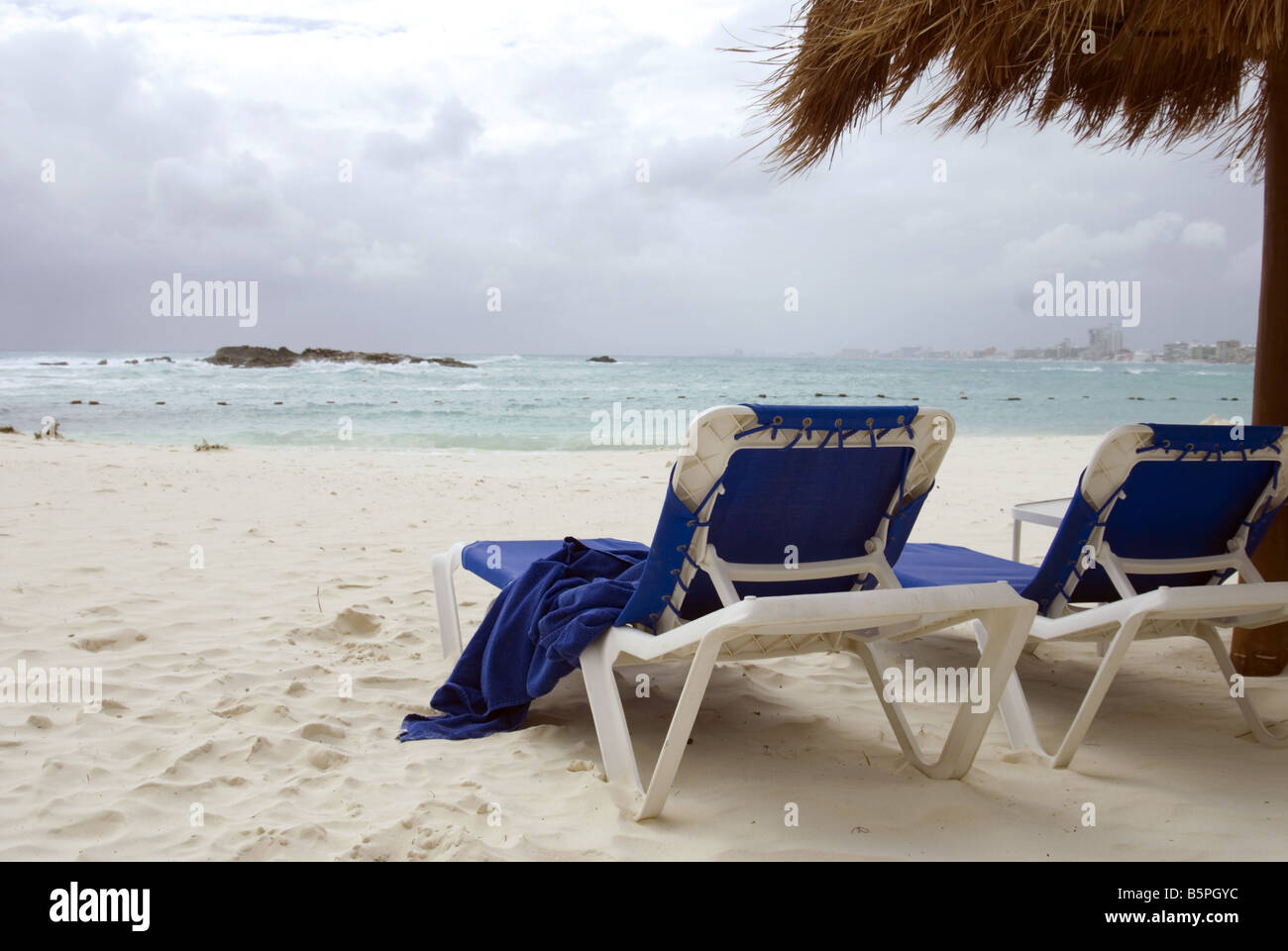beach lounge chairs sit empty on shore of caribbean ocean in cancun mexico with stormy skies and palapa - Beach Lounge Chairs