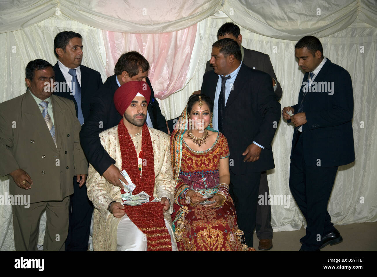 Wedding Guests Give Gifts Of Cash To The Bride And Groom At A Traditional Sikh