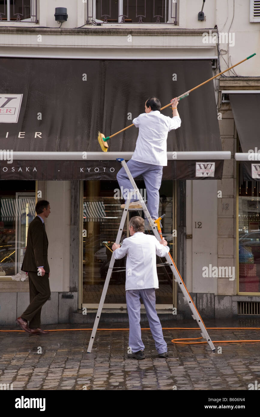 Shop Workers Clean The Awning Of A In Place Du Grand Sablon Bruxelles Belgium 44
