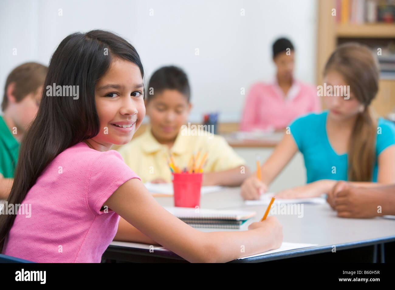 Students in class taking notes with teacher in background ...