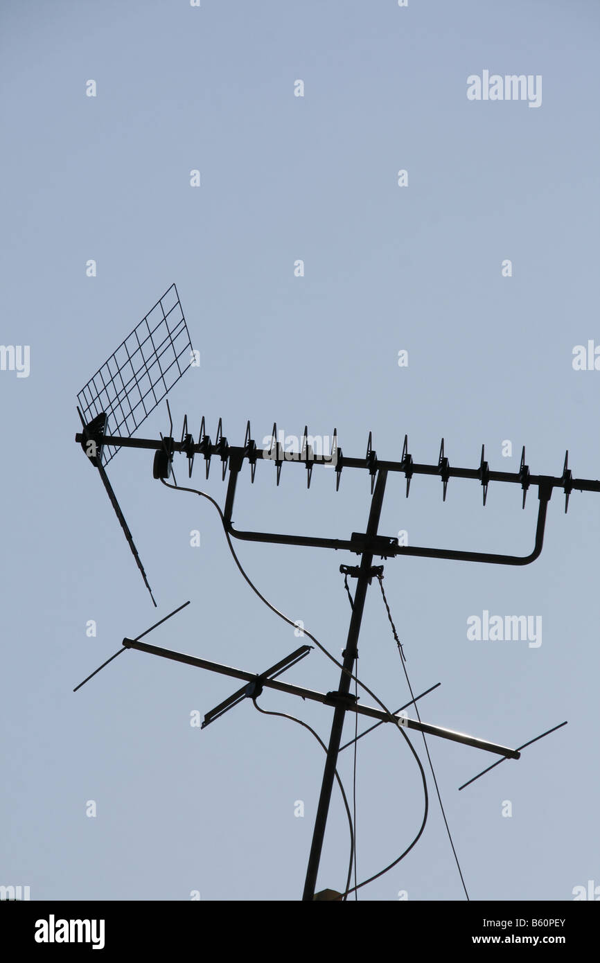 Stock Photo   Two Television Aerials Antennas On Roof Top And Blue Sky