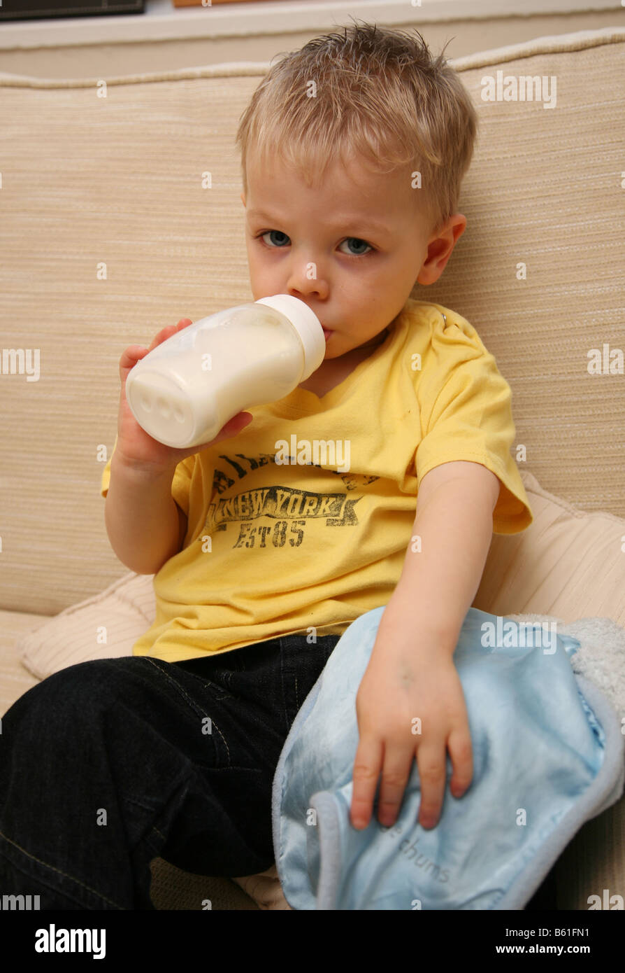 Tired 2 year old boy drinking warm milk from the bottle ...