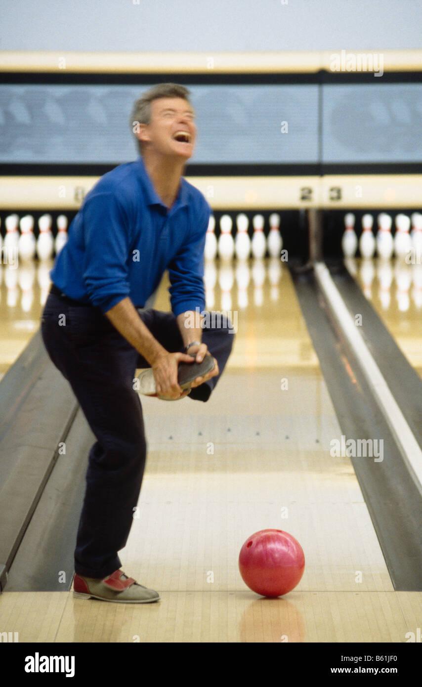 Man Dropping Bowling Ball On Foot At Bowling Alley Stock