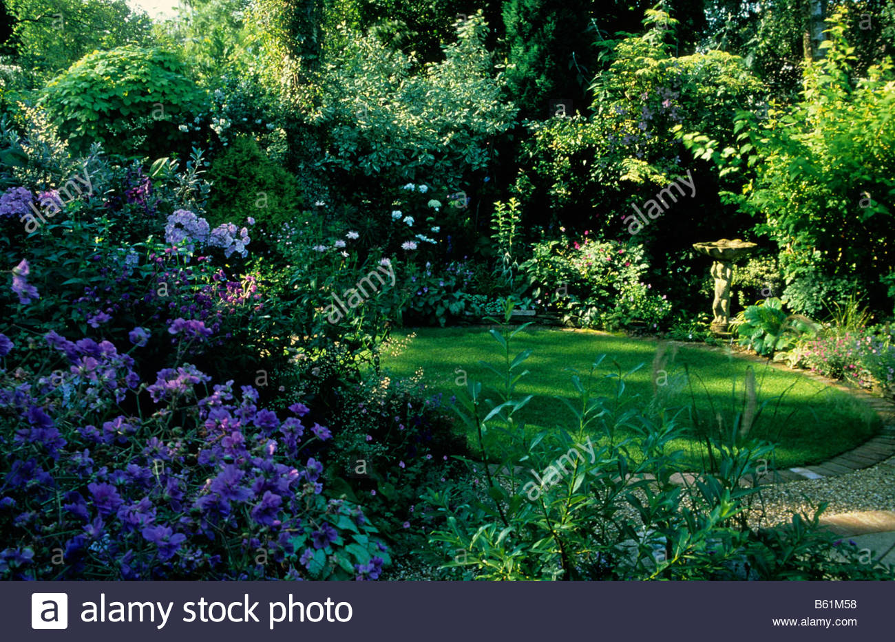 Ladywood Hampshire Small Shady Garden With Formal Circular Lawn Border  Borrowed Landscape Of Woods Beyond Fence