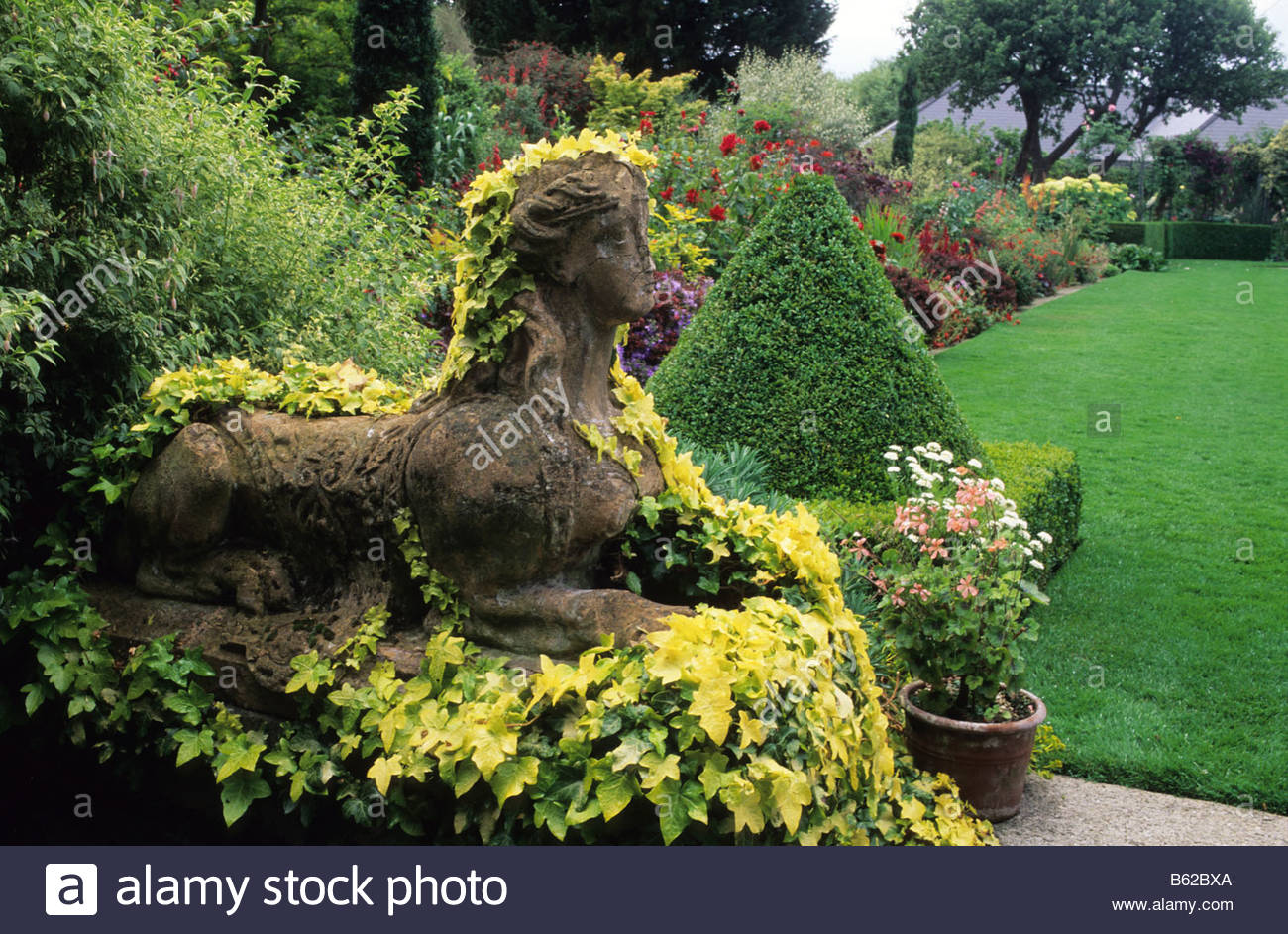 Stock Photo   The Dillon Garden Dublin Ireland Large Town Suburban Garden  Stone Sphinx Statue Covered With Hedera Helix Buttercup And Pyramid