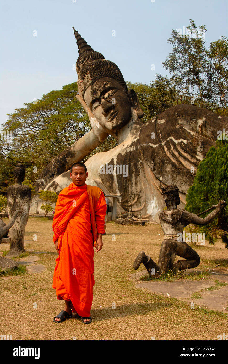 Buddhist monk statue stock photos buddhist monk statue stock buddhist monk wearing an orange robe in front of a reclining buddha statue buddha park kristyandbryce Image collections