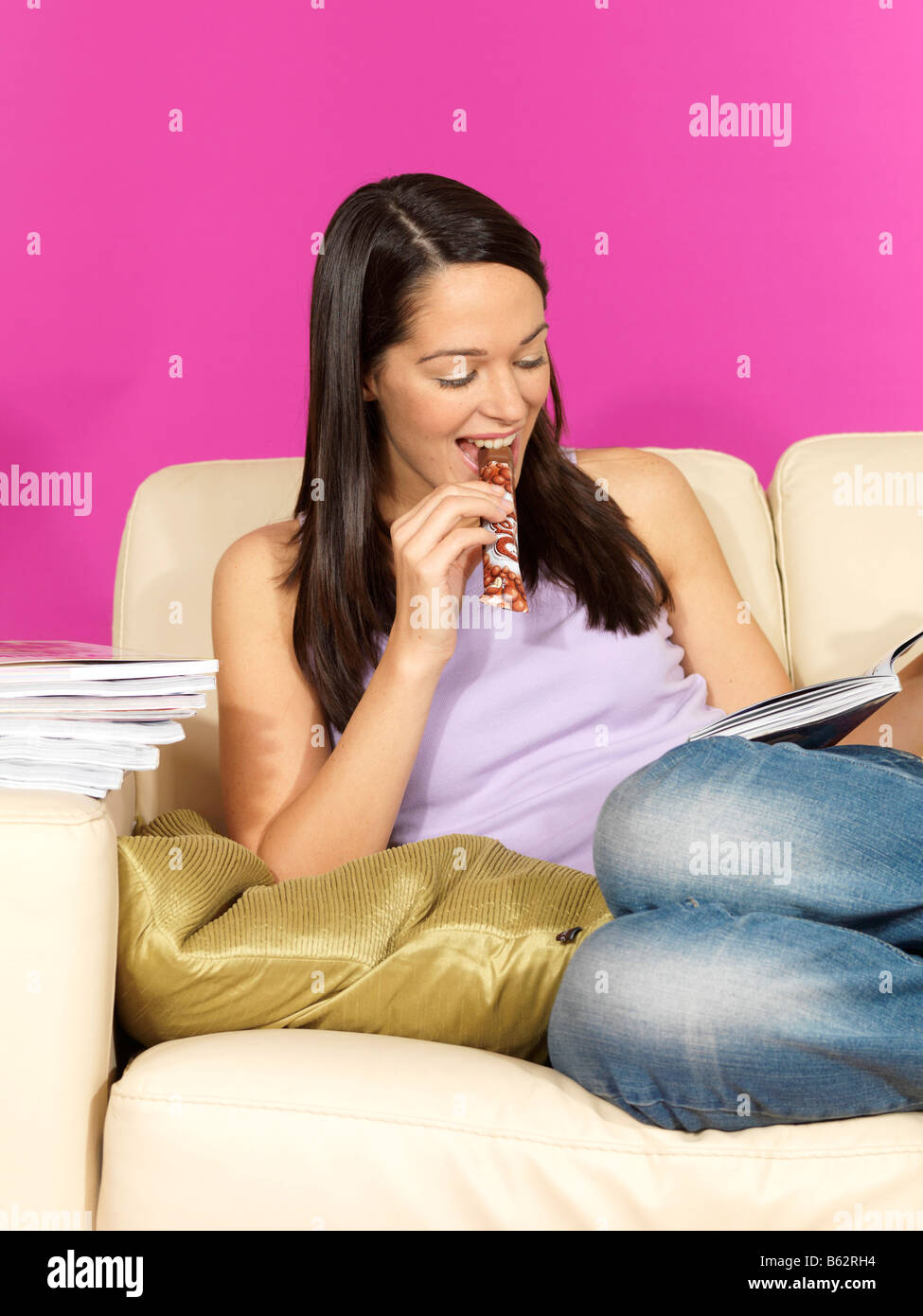 Young Woman Reading a Magazine Eating Chocolate Model Released ...