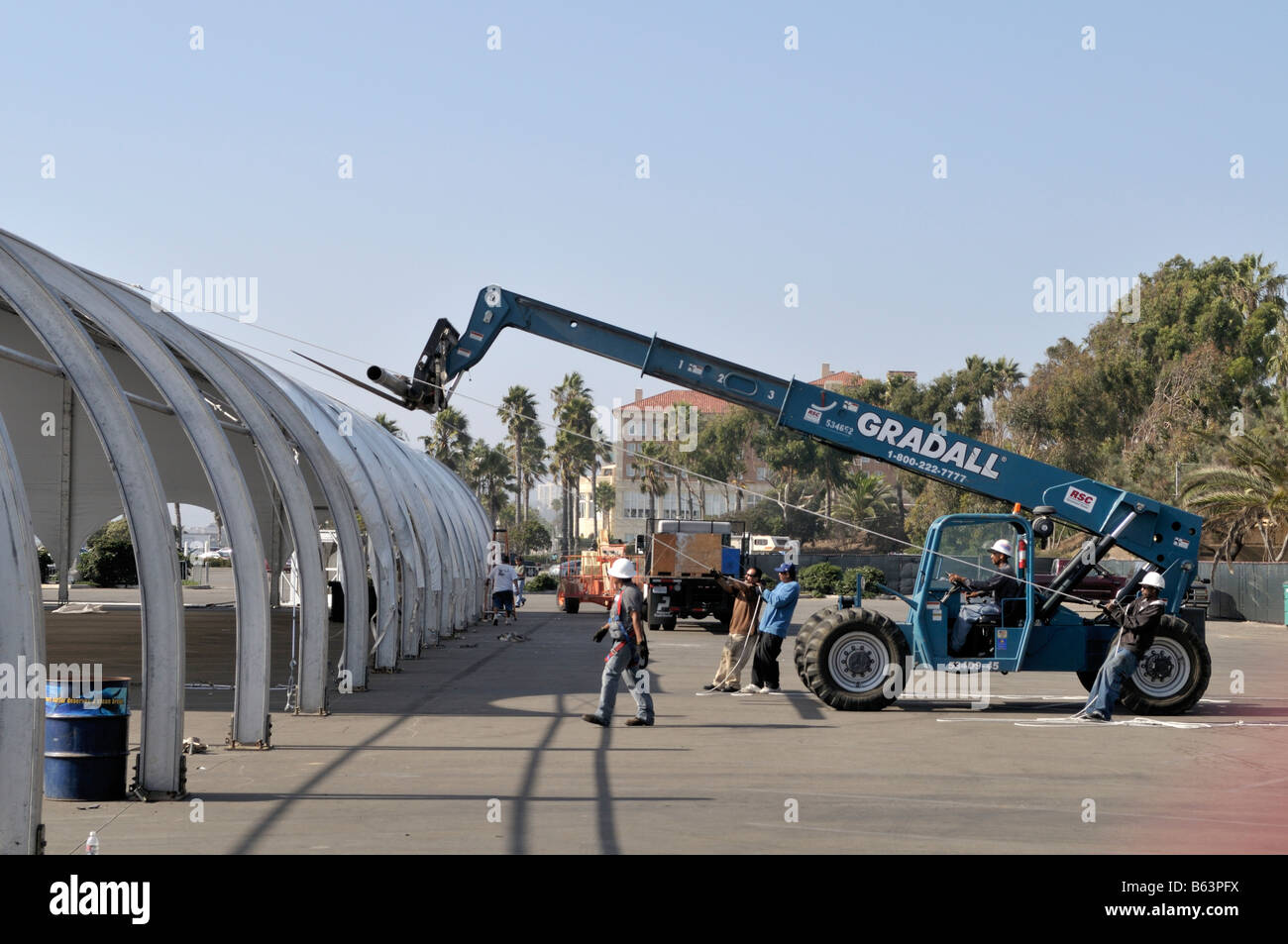 A very large tent structure is being raised at a parking lot on the Santa Monica Beach & A very large tent structure is being raised at a parking lot on ...