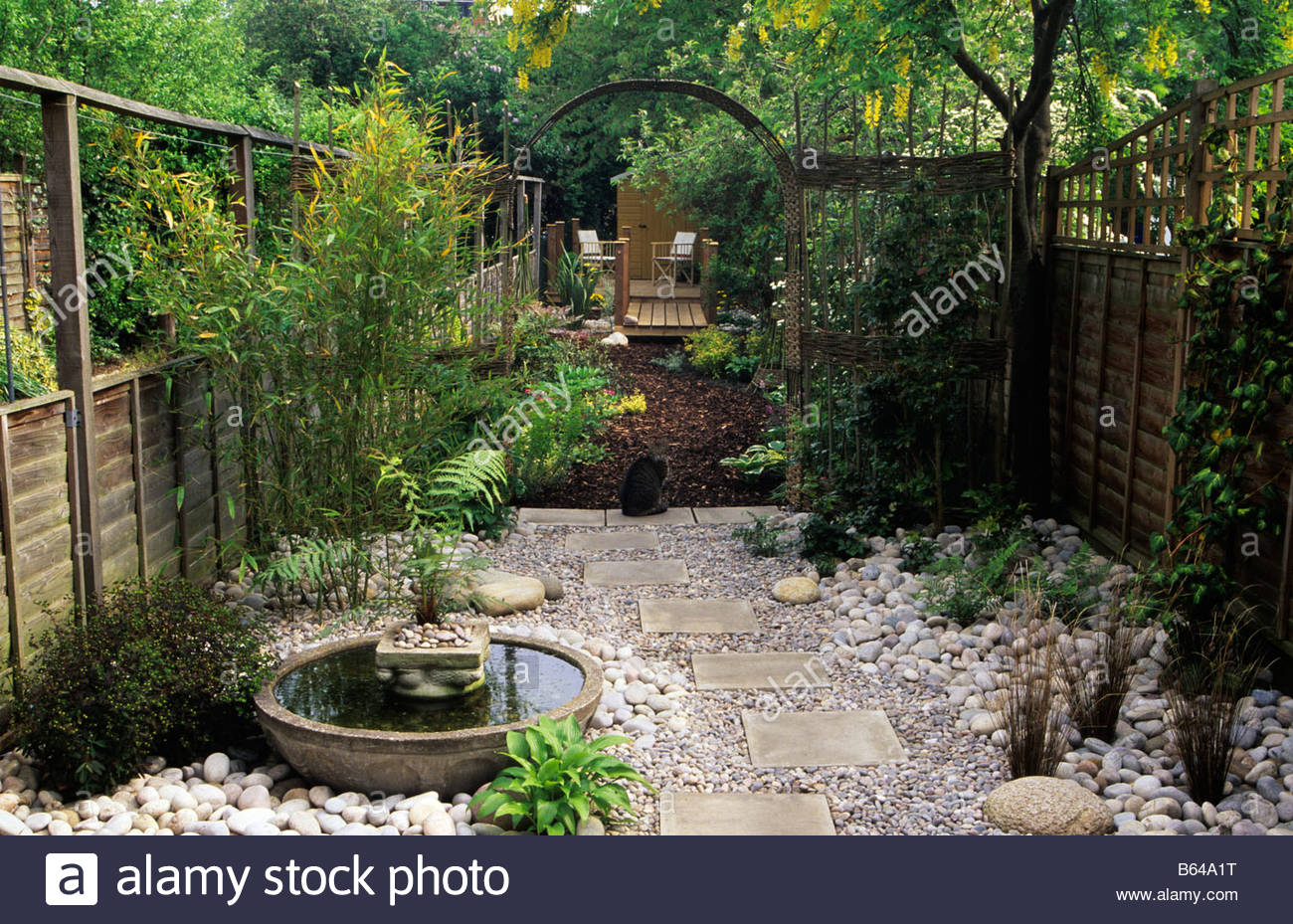 Hallowell Rd Middx design Alan Titchmarsh Japanese style garden with arch  pebbles stones cat wooden fence stepping stones water