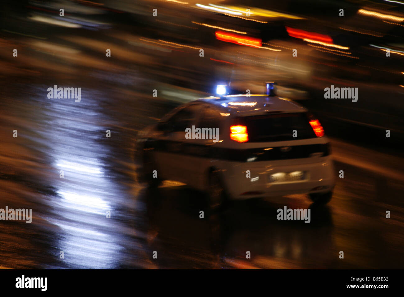 Fast Police Car Driving In Heavy Rain At Night In Town In Italy