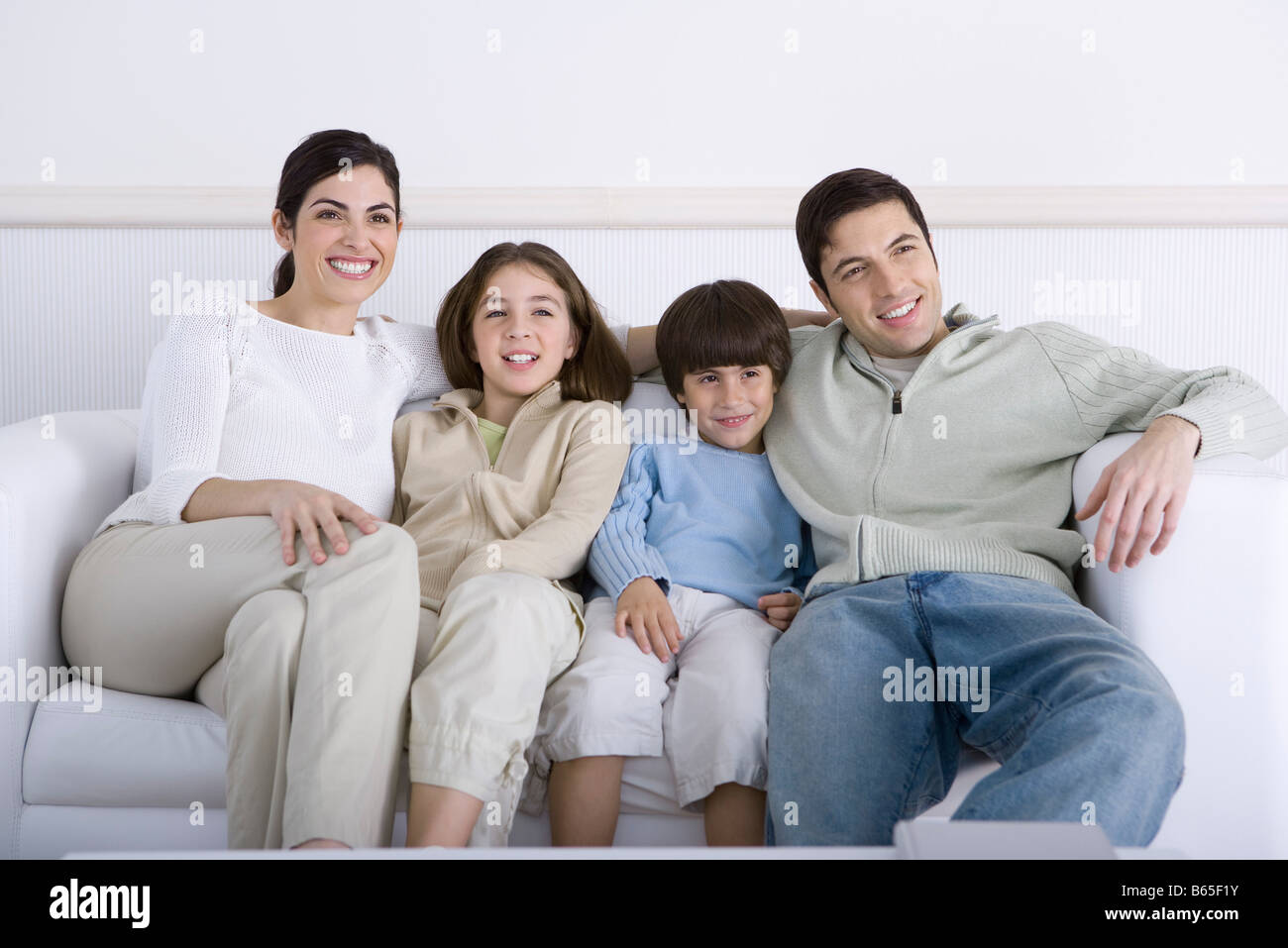 Great Family Sitting Together On Sofa, Looking Away