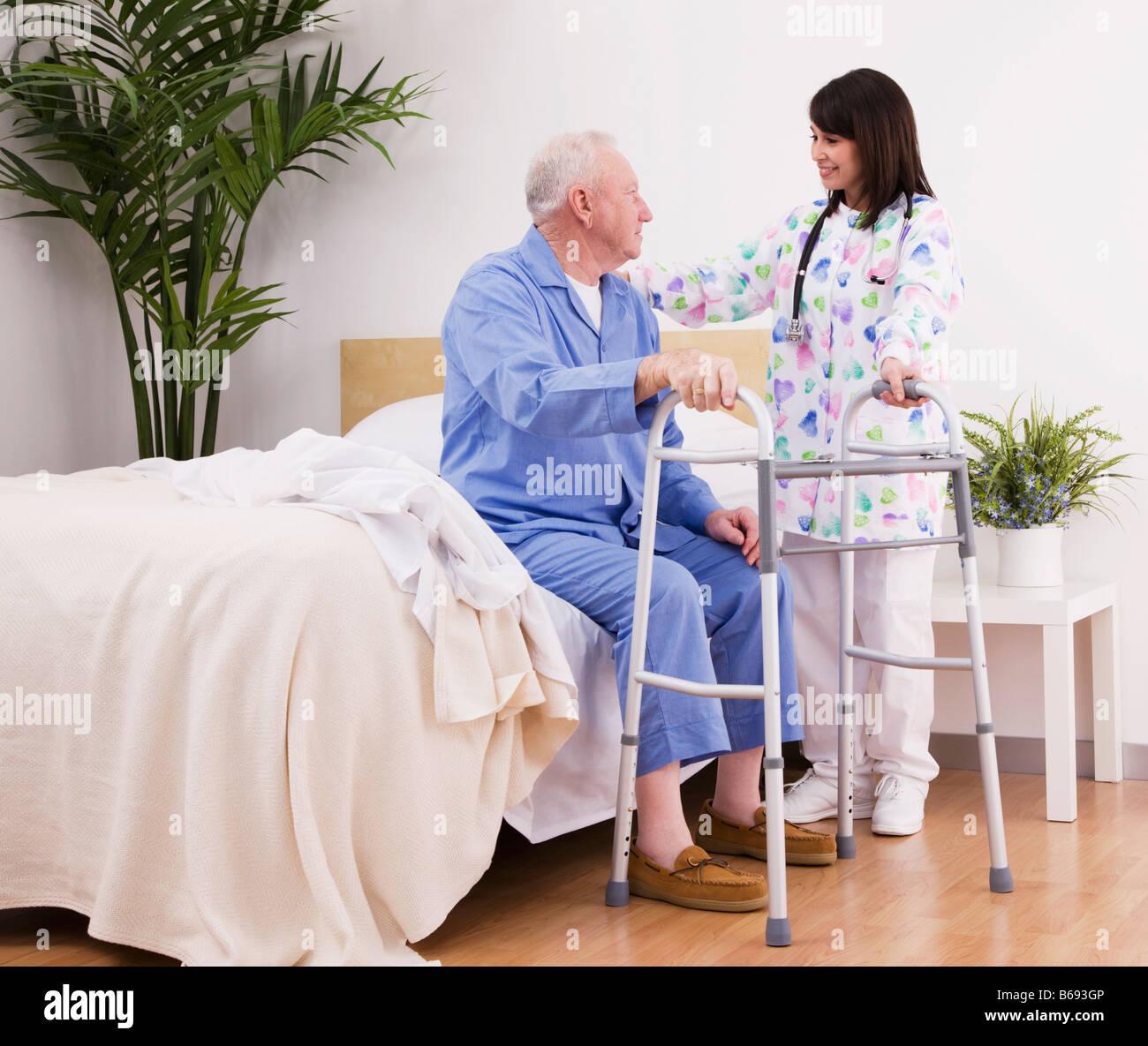 nurse helping senior man walk with frame stock photo royalty free