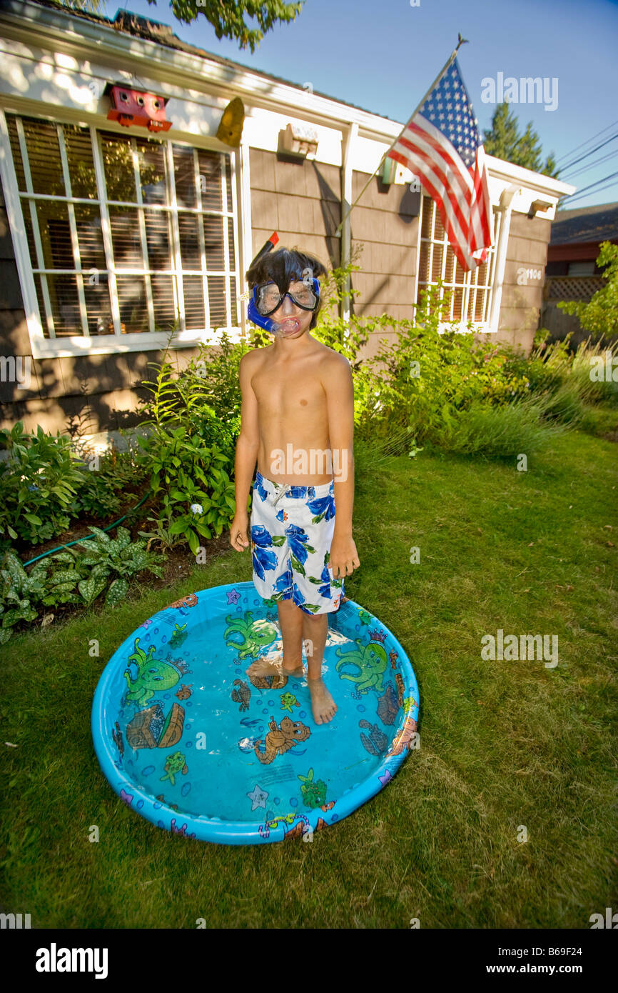 boy wearing snorkel and standing in a wading pool stock photo
