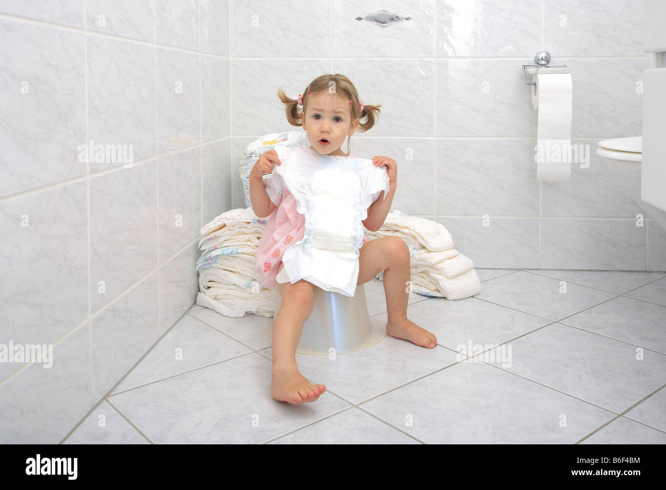 potty training, little girl sitting on potty, looking at a ...