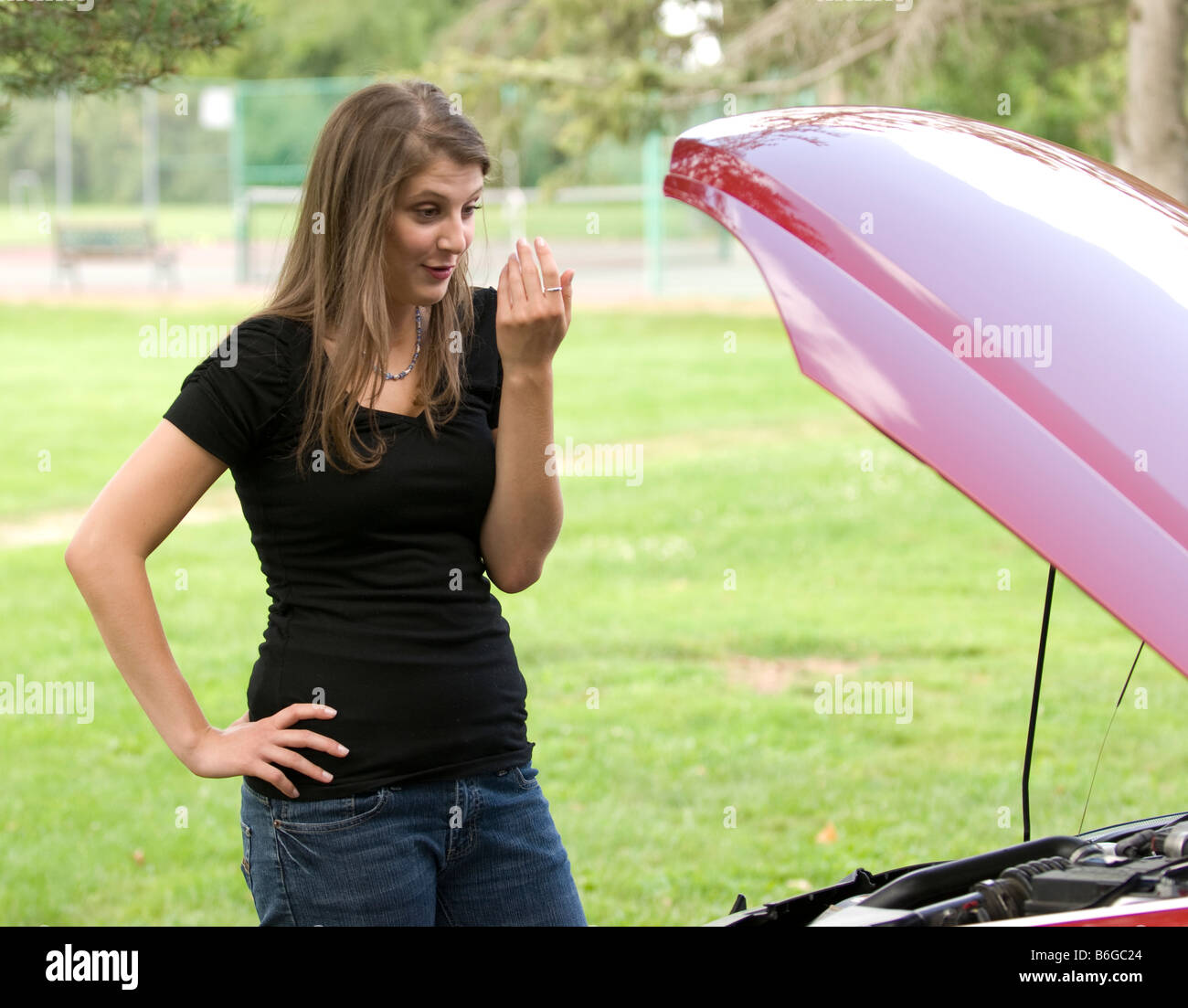 Young Woman Looking Under The Hood Bonnet Of A Car