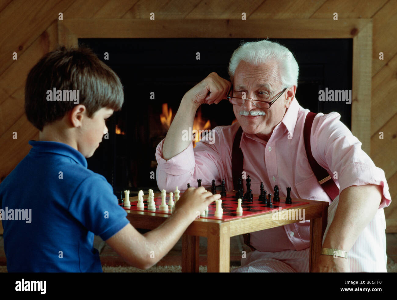 Grandfather and grandson play chess in front of fireplace Stock ...