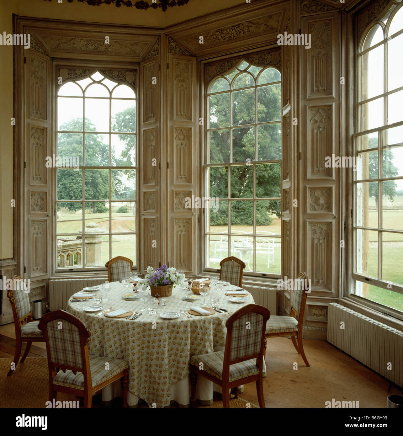 Tall country dining room sets - Stock Photo Upholstered Chairs And Table Set For Lunch In Front Of Tall Gothic Windows In Large Country Dining Room With View Of Garden