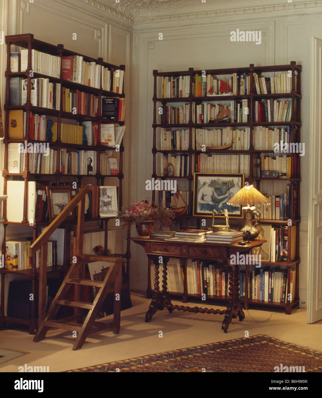Lighted lamp on table in library study with tall bookshelves and lighted lamp on table in library study with tall bookshelves and old wooden library steps geotapseo Image collections