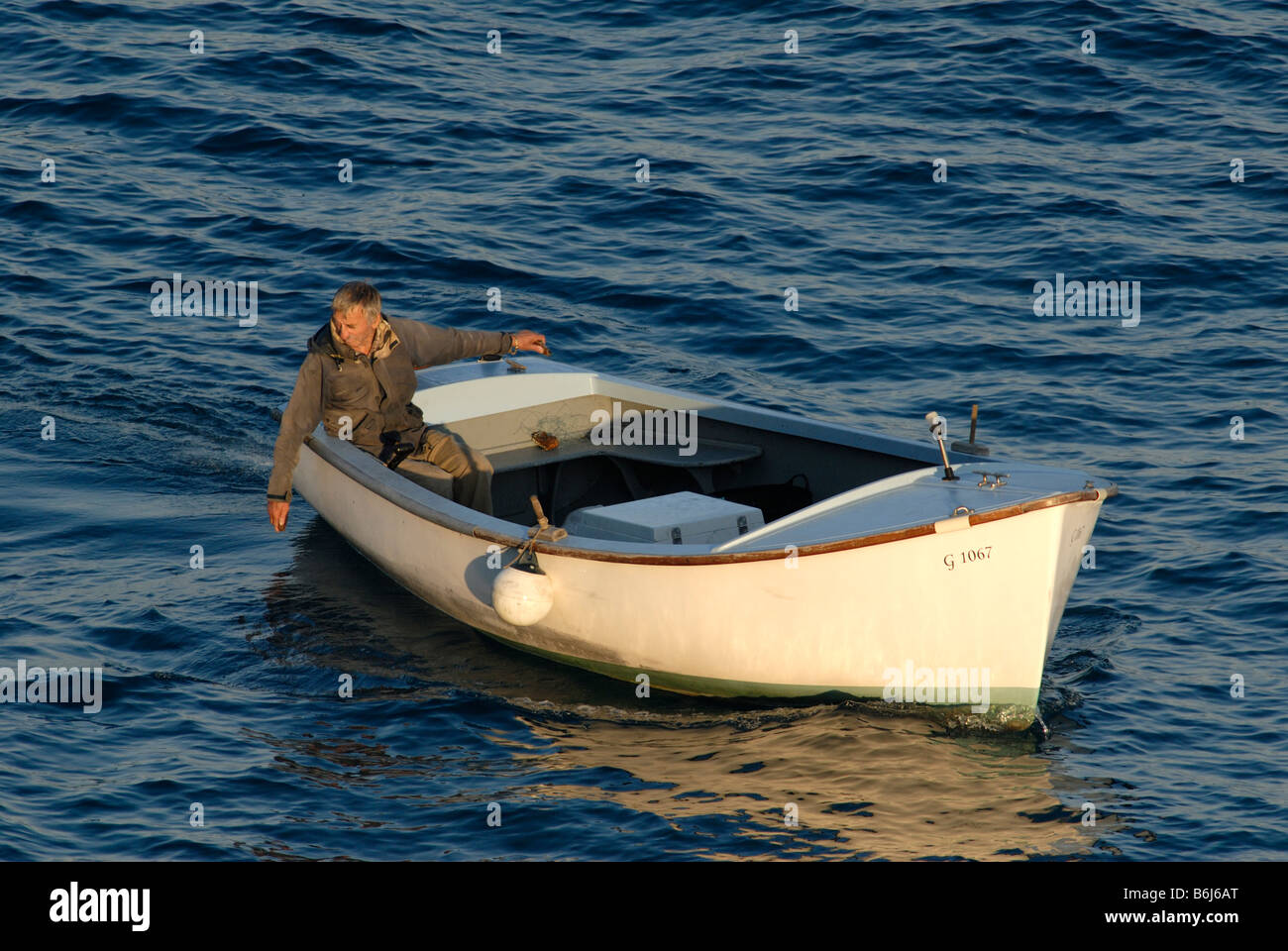 Old man in small boat fishing with hand line stock photo for Hand line fishing
