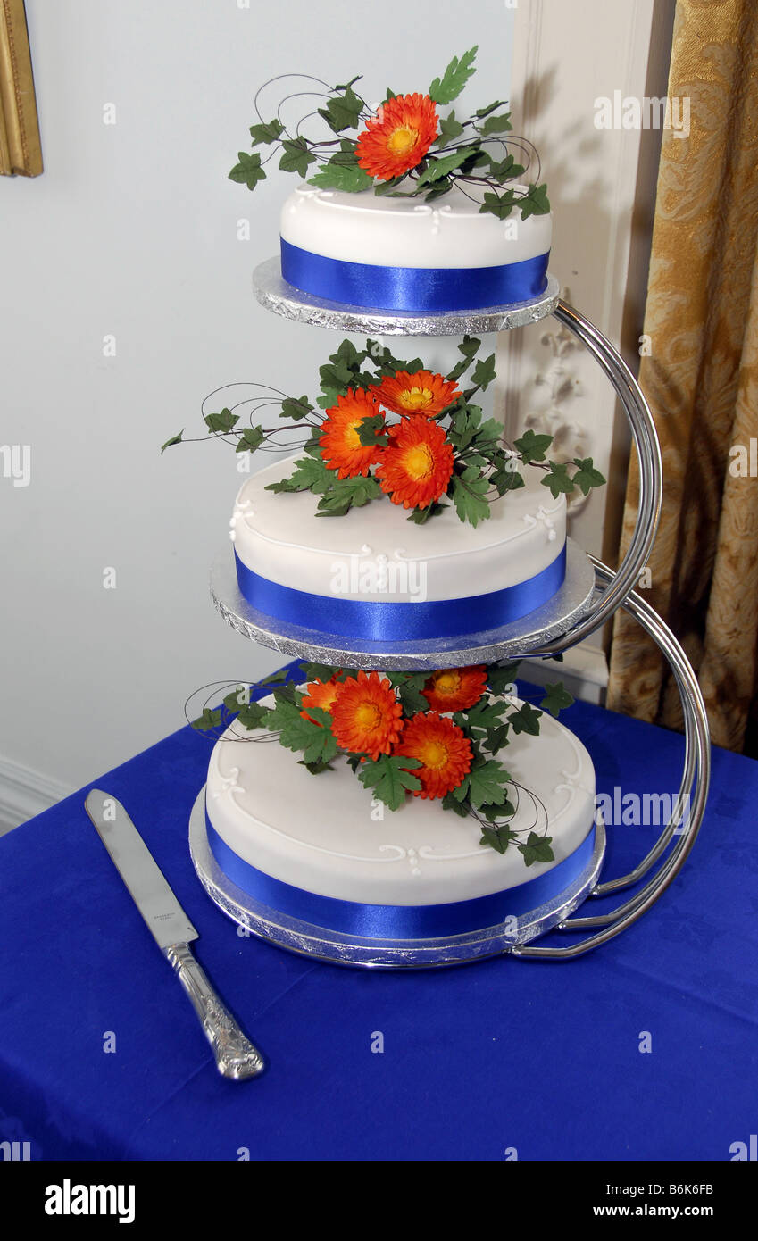Three tiered iced wedding cake on silver stand decorated with ...