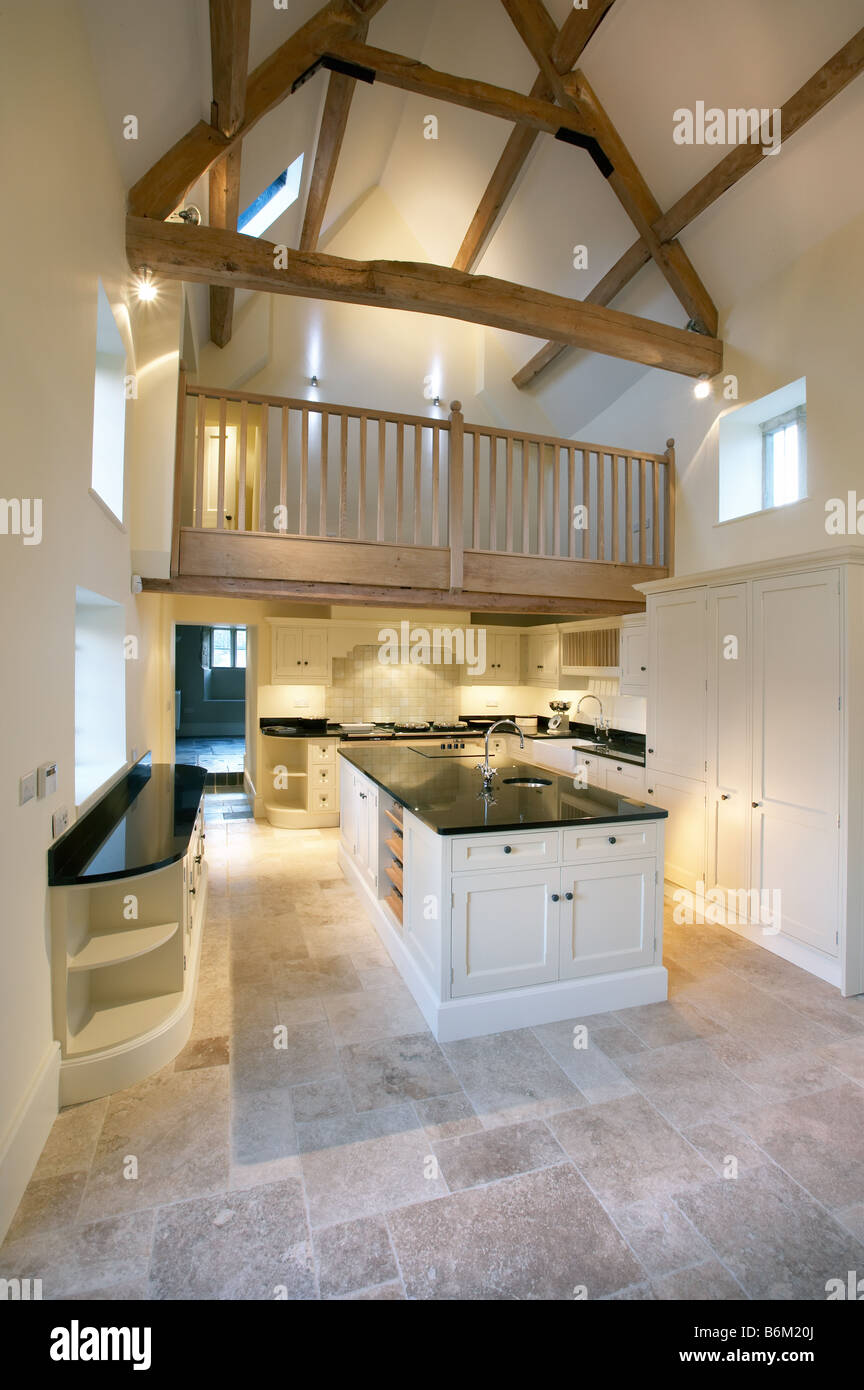 Shaker style kitchen in cream neutral colours, limestone floor double  height mezzanine floor balcony gallery
