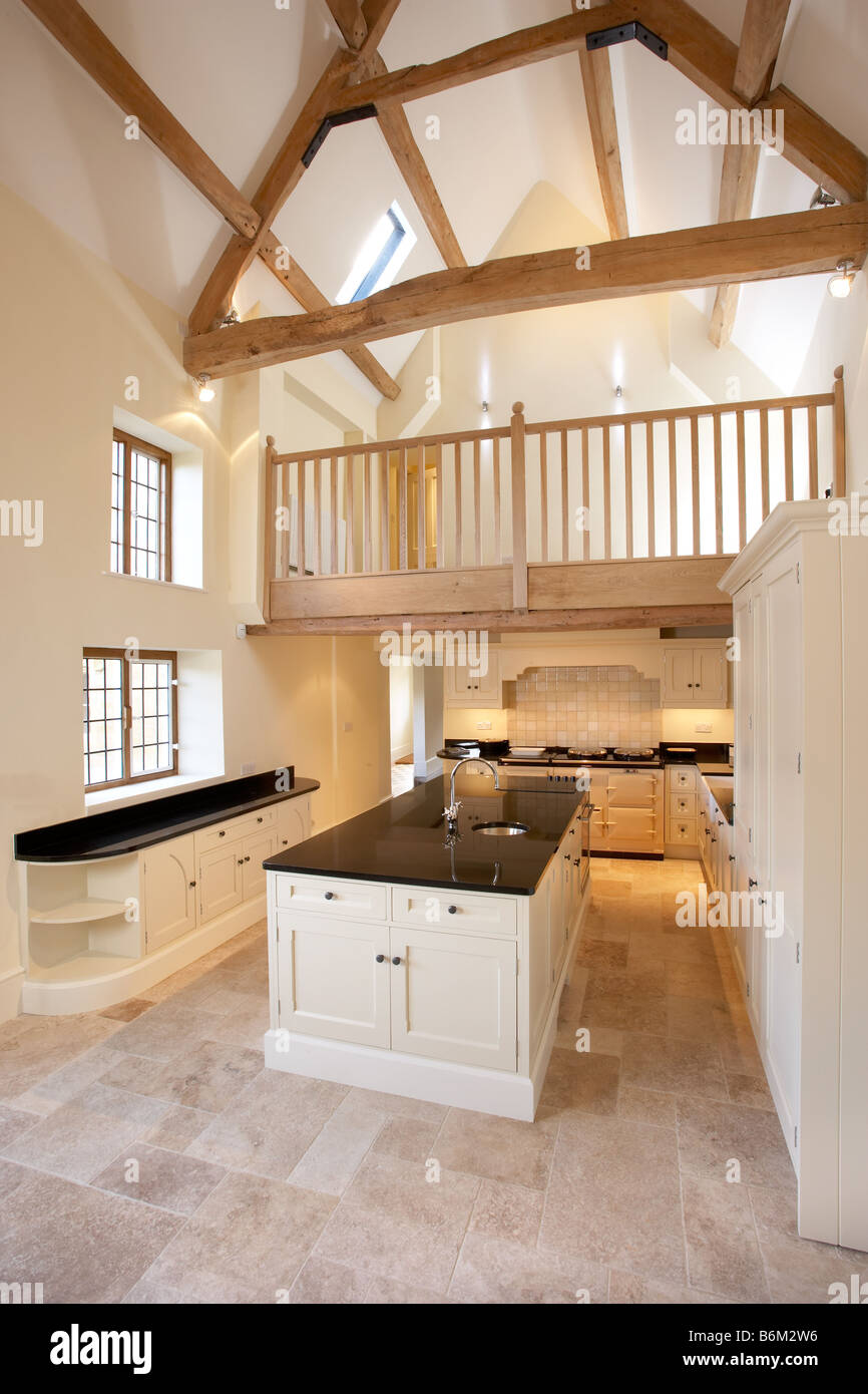New cream kitchen in double height room with beams mezzanine floor  limestone floor aga black granite worktop shaker style
