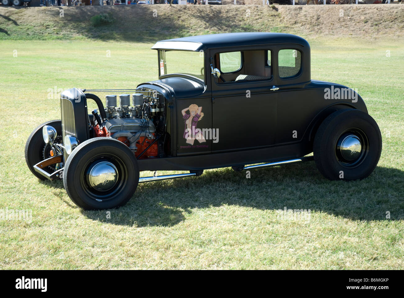 An old hot rod sits in the middle of a field at a car show Stock ...