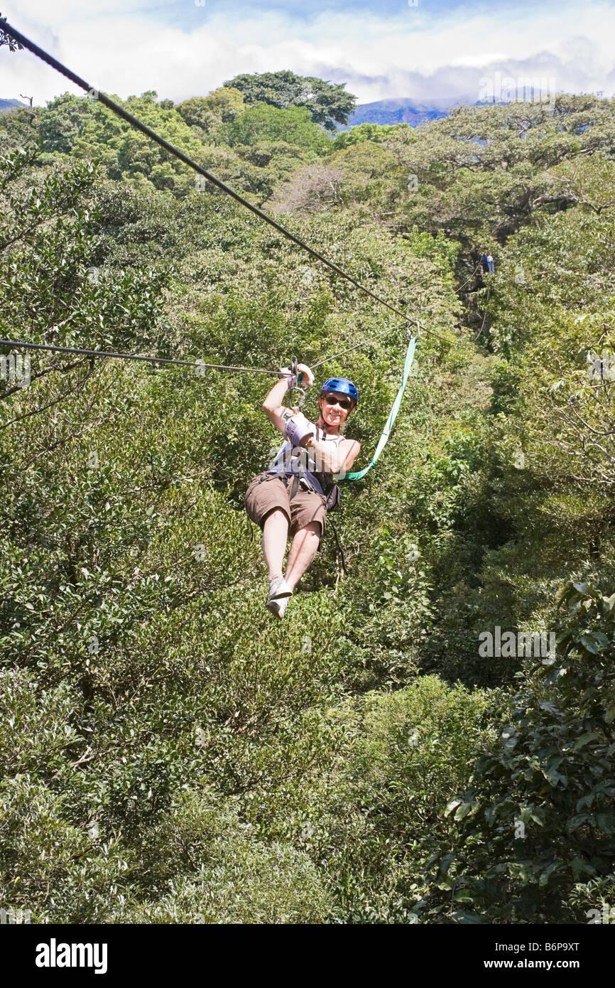 Woman zips through rainforest canopy on zipline tour at Buena Vista Lodge in Rincon de la Vieja forest in Costa Rica & Woman zips through rainforest canopy on zipline tour at Buena Vista ...
