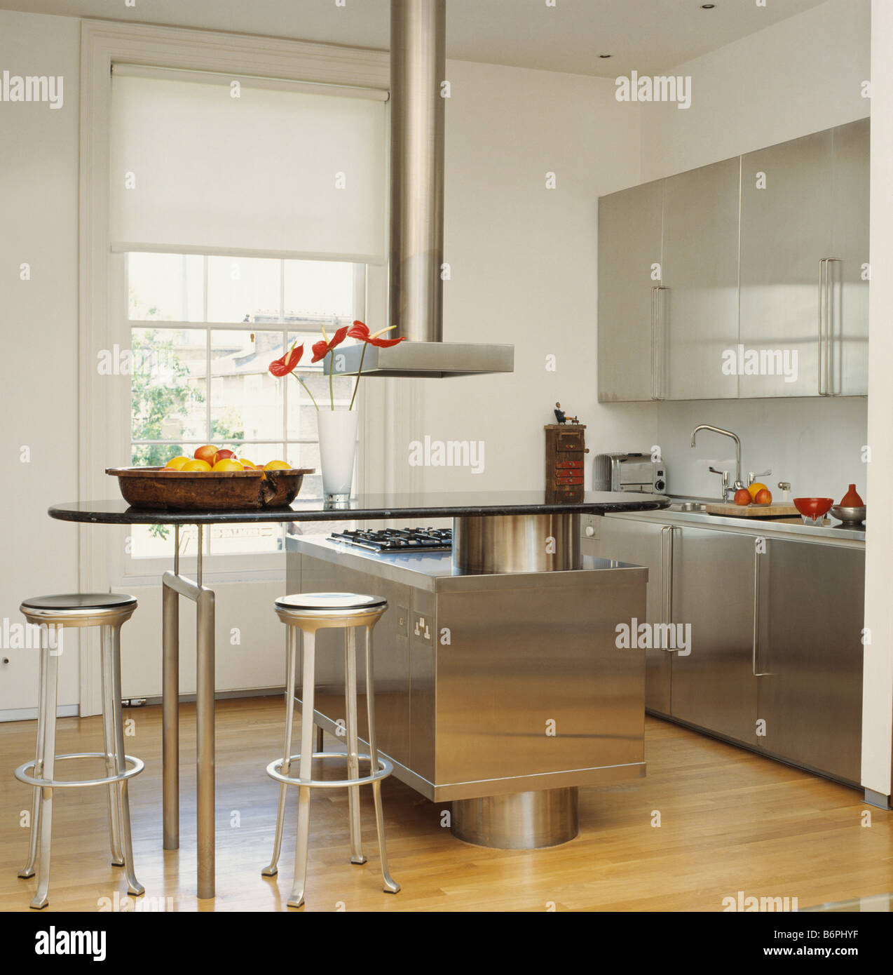 Metal Stools At Glass Breakfast Bar In Modern White Kitchen With Stainless  Steel Fitted Units And Wooden Flooring