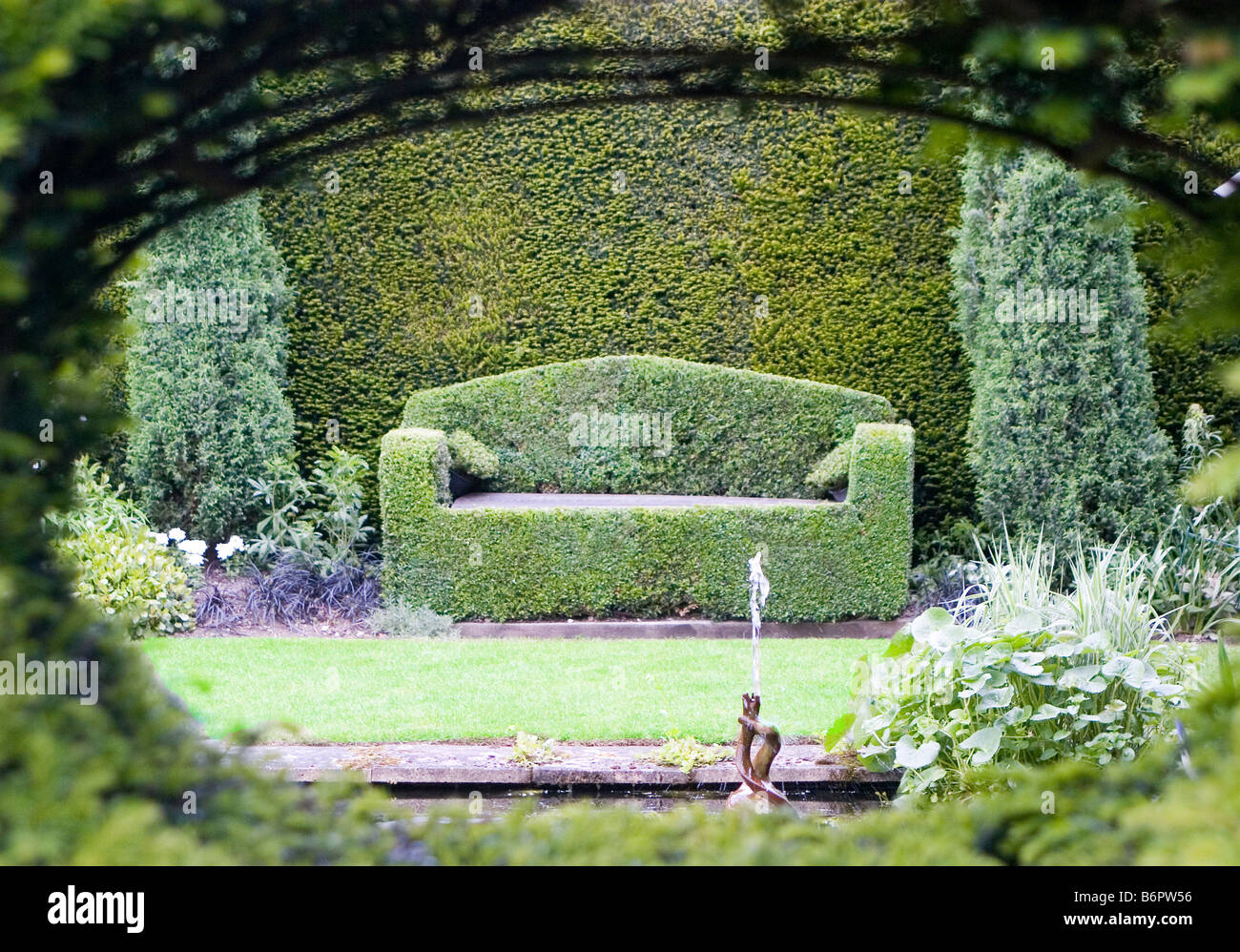 box topiary garden seat with cushions viewed through opening in hedge opposite