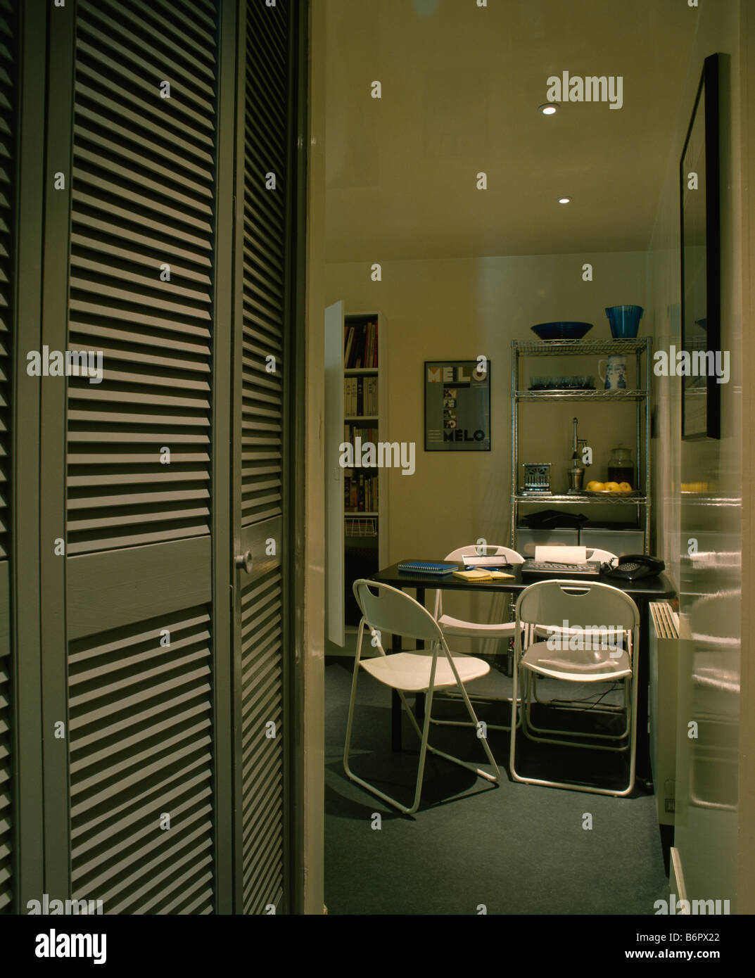 Cupboard With Louvre Doors At Entrance To Small Modern White Dining Room Metal Folding Chairs And Black Table