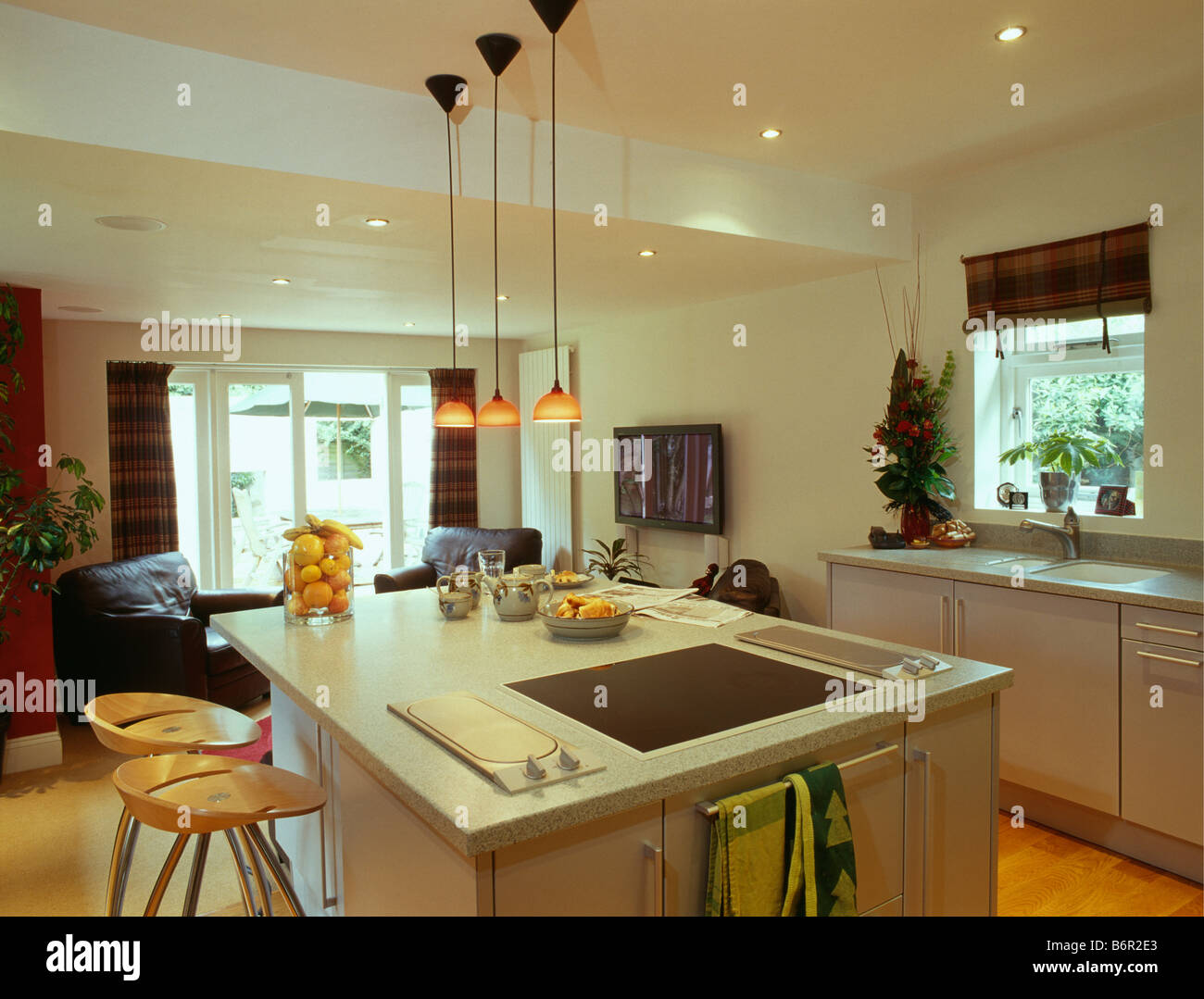 Small Orange Pendant Lights Above Island Unit With Fitted Halogen Hob In Modern White Kitchen