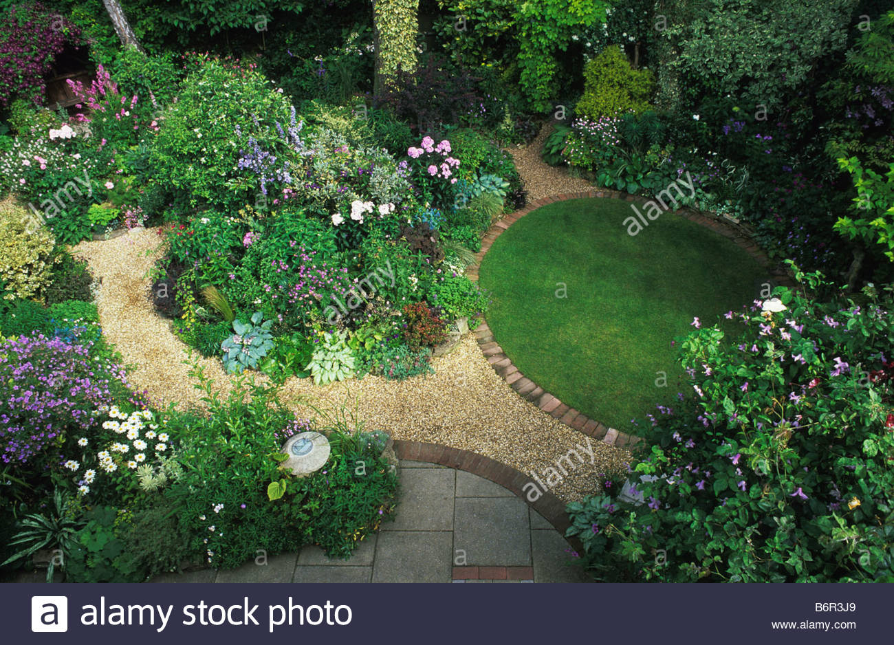 ladywood hampshire small semi shady garden with two circular design elements lawn and flower bed with
