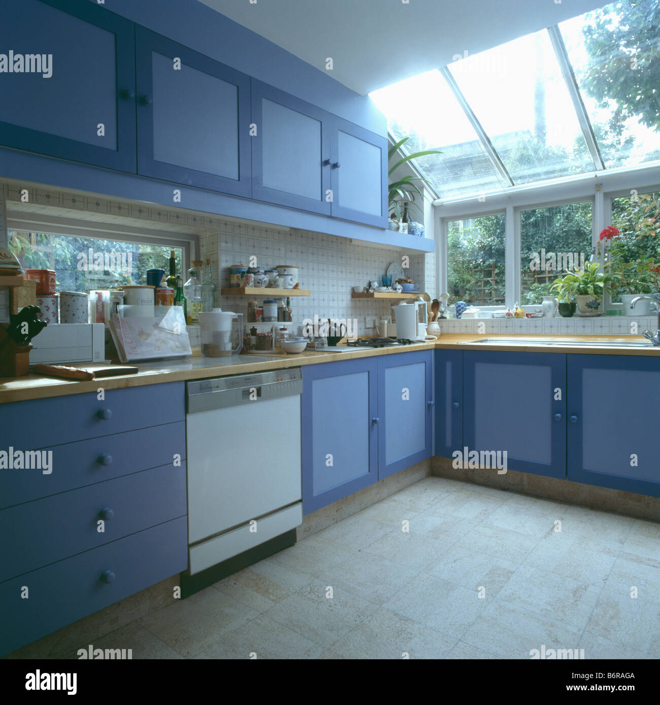 Blue Fitted Cupboards In Kitchen Extension With Glass Skylight And Stock Photo, Royalty Free