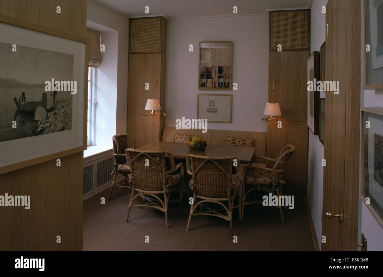 Stock Photo   Wall Lights In Small Dining Room With Cane Chairs And Wooden  Table