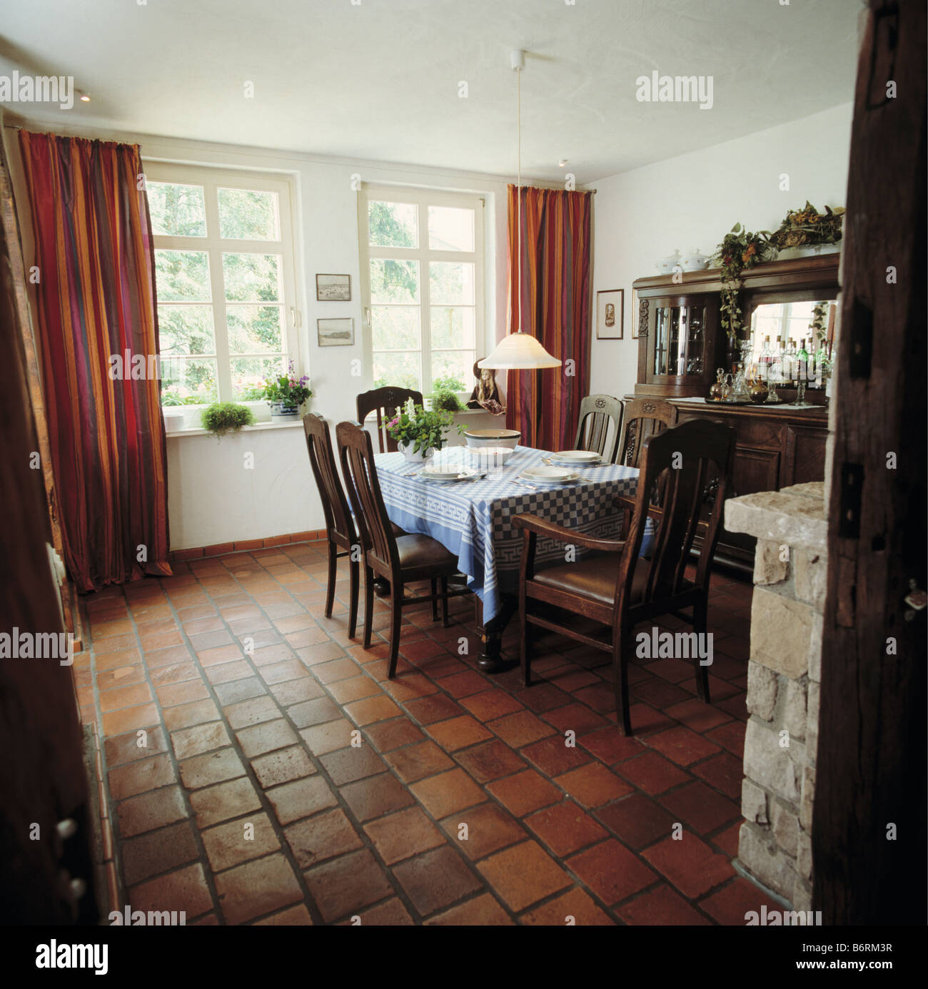 Terracotta Tiled Floor In Country Dining Room With Red Curtains