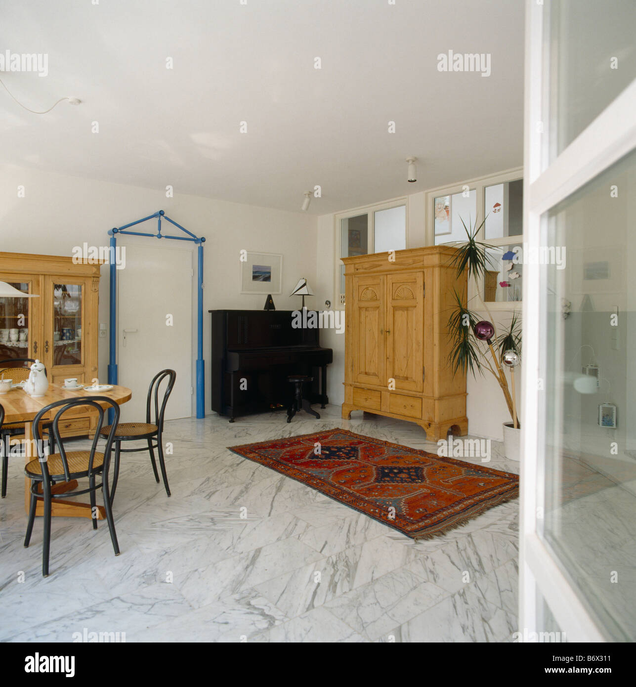 Bentwood Chairs And Red Oriental Rug On Marble Flooring In Modern White Dining Room With Large Pine Cupboard