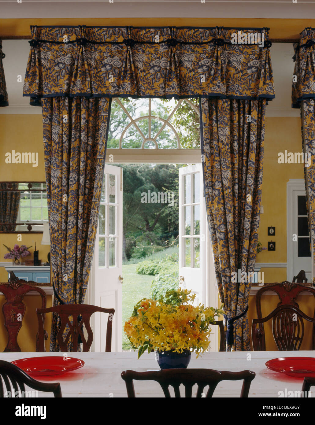 Patterned Curtains At Open French Doors With View Of Garden In Yellow Country Dining Room
